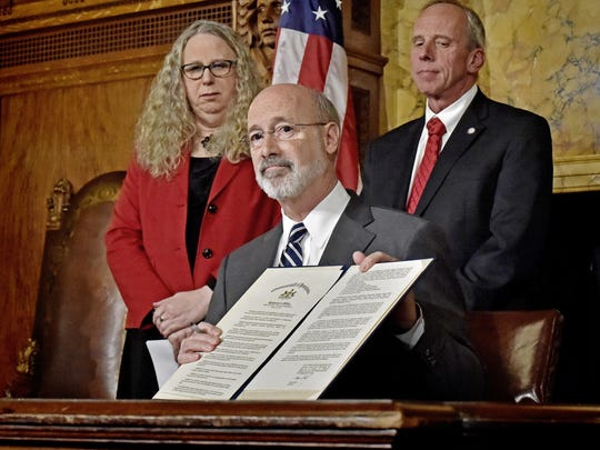 Pennsylvania Gov. Tom Wolf shows the document he signed declaring a state of emergency in the state's fight against heroin and opioid addiction during a news conference at the state Capitol in Harrisburg, Pa., Wednesday, Jan. 10, 2018. In the background are Acting Secretary of Health and Physician General Dr. Rachel Levine, left, and Pennsylvania Emergency Management Agency Director Richard D. Flinn Jr. Wolf signed an order for the 90-day disaster declaration, widening access to the state's prescription drug monitoring program and making it easier for medical professionals to get people into drug treatment more quickly. (Blaine T. Shahan/LNP via AP)
