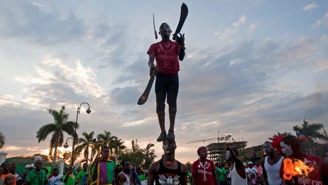 A performer juggles machetes while standing on the top of his partner's head, during Carnival celebrations in Port-au-Prince, Haiti.