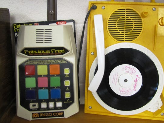 A handheld electronic game, left, and a small record