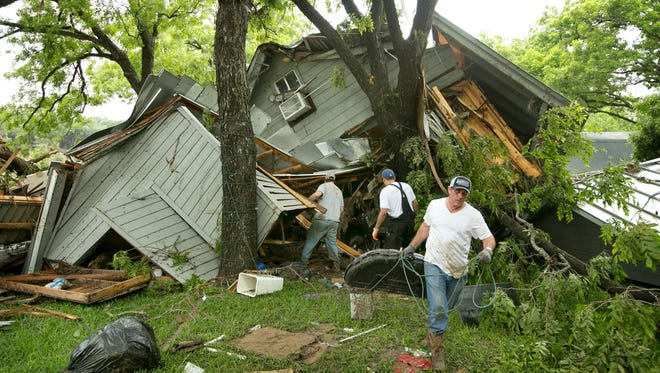 Jeremy Steele, left, Ric Jaime, center, and Keith McNabb salvage belongings at their friend Mike Cook's house near Wimberley, Texas, Sunday, May 24, 2015. About 350 homes in the town of Wimberley were washed away by flash floods along the Blanco River, which rose 26 feet in just one hour and left piles of wreckage 20 feet high, Texas authorities said.