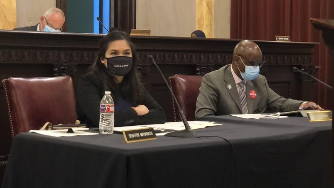 "State Sen. Tina Maharath, D-Canal Winchester, left, wears a mask that says ""hate is a virus"" during a committee hearing in late June."