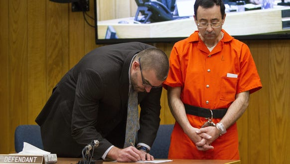 Defense attorney Matthew Newberg, left, signs court