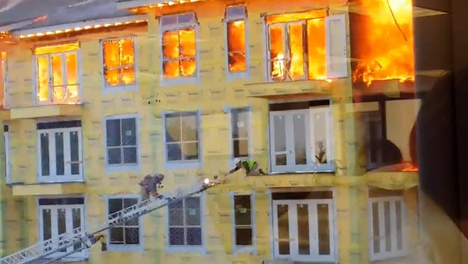 In this image taken from video provided by Karen Jones, construction supervisor Curtis Reissig reaches for a ladder to escape a five-alarm blaze at a construction site Tuesday, March 25, 2014, in Houston. T
