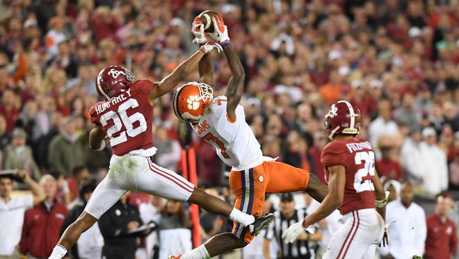 Clemson Tigers wide receiver Mike Williams (7) catches a pass between Alabama Crimson Tide defensive back Marlon Humphrey (26) and defensive back Minkah Fitzpatrick (29)  in the 207 College Football Playoff National Championship Game at Raymond James Stadium.