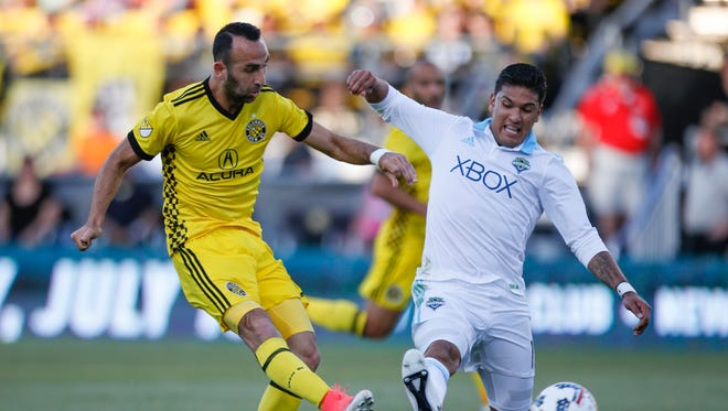 Columbus Crew forward Justin Meram (9) shoots past Seattle Sounders defender Tony Alfaro (15) for a goal during the first half of Wednesday's game.