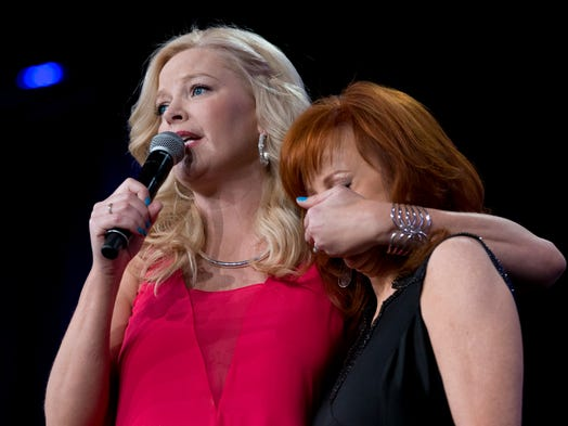 Actress Melissa Peterman, left, jokes with Reba McEntire while auctioning dinner off with McEntire during Muhammad Ali's Celebrity Fight Night at JW Marriott Desert Ridge Resort and Spa in Phoenix.