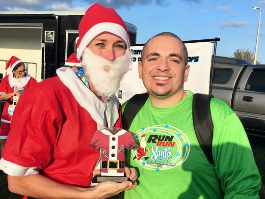 Mike Acosta, right, is the creator of the Run Run Santa race that takes place before Christmas. He donates a large portion of the proceeds to charity through his Power of Pizza Charities.