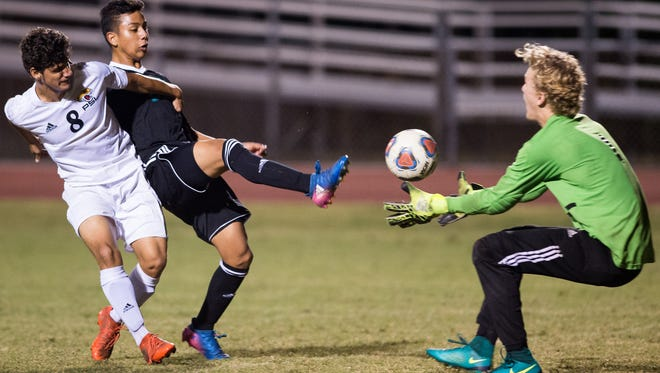 Jensen Beach's Dennis Hernandez (center) pushes the ball past Port St. Lucie goalkeeper Zack Knudsen on his way to a goal, despite defensive efforts by Victor Alvarado (left), during the first half of the high school boys soccer game Tuesday, Dec. 19, 2017, at Port St. Lucie High School.