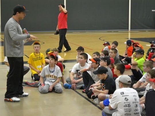Jason Berken, left, talks to children at his baseball