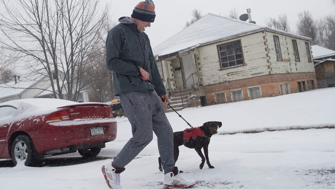 Sam Strus and his dog, Nova, on Parker Street as snow continues to fall in Fort Collins on Thursday, December 21, 2017.