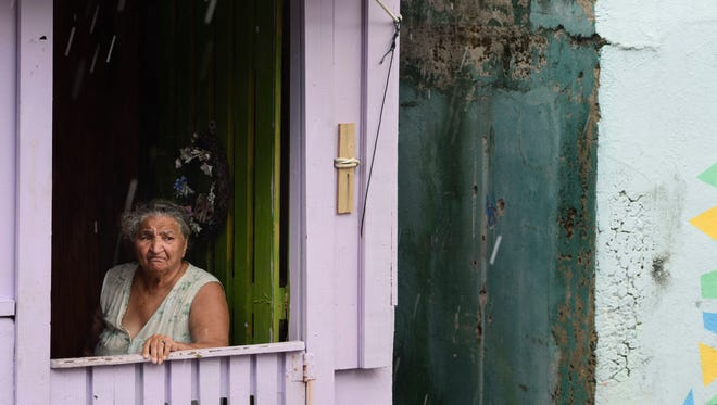 La Perla resident Maria Antonia Perez Rivera looks out from her battered residence in San Juan, Puerto Rico, on Sept. 25, 2017.
