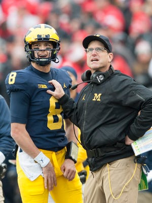 Michigan quarterback John O'Korn and head coach Jim Harbaugh confer during Saturday's game against Ohio State, which ended in a 31-20 Buckeyes' victory.
