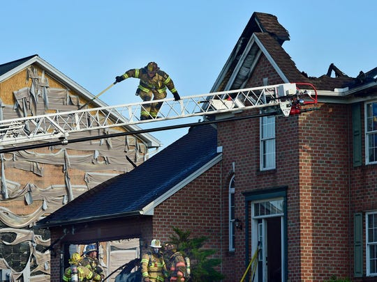 A firefighter works from a ladder at a home the caught