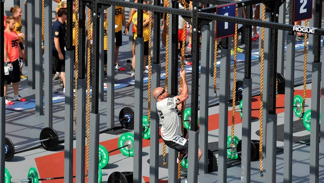 In a file photo from 2013, competitors climb ropes during team competitions at the CrossFit Games at StubHub Center.