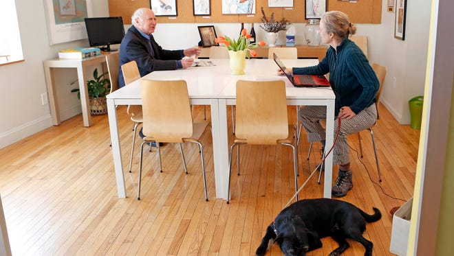 Robert Kimmel, the chairman of the editorial board of The Hudson Independent, chats with improv teacher Lynne Lori Sylvan as her dog Chester Chestnut lies by her side in the conference room at W@tercooler on Feb. 25 in Tarrytown. W@tercooler is a boutique-style coworking space that opened in 2005.