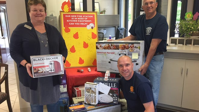 From left, Jane Jandrin, bank manager for Nicolet Bank in Brussels, is pictured with Jim Wautier and Curt Vandertie of the Brussels-Union-Gardner Fire Station with items from a giving tree the bank sponsored  to collect items to stock the kitchen at the new BUG fire station. An open house for the station is planned for June 24.