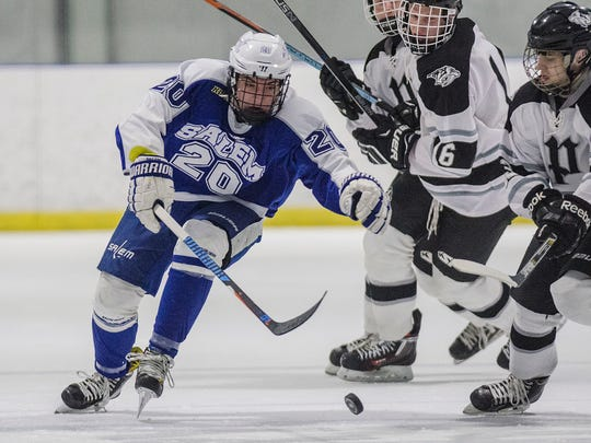 Salem's Logan Sowa (20) chases the puck with pressure from Plymouth players.