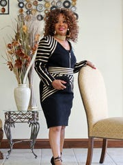 Maxine Lewis shows off a black and gold form fitting knee length stretch denim dress with faux leather trim, round neck and hidden zipper by Tally Taylor.