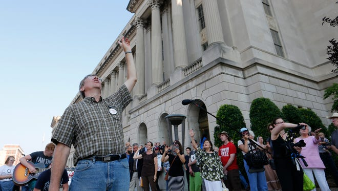 Cal Zastrow leads a group of protesters in song in front of the federal courthouse. The group is in Louisville to protest at the EMW Women's Clinic as well as fight in court against a protective buffer zone in front of the abortion clinic. July 24, 2017.