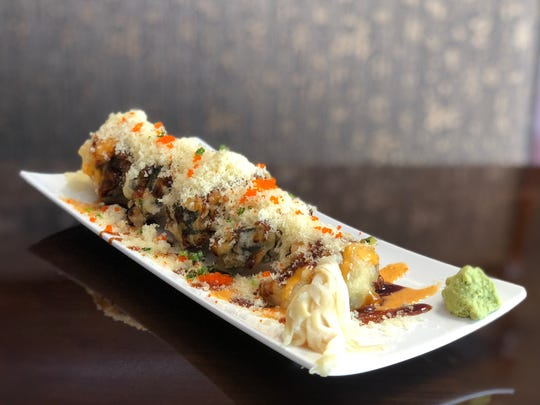 The Dynamite Roll is warm and deep fried, with salmon, krab meat, cream cheese with crunchy tempura bits,  spicy mayo, Tobika, scallions and eel sauce.