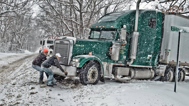 Lori Lammon and Monty Stahelin of Community Sharing add a little humor to a difficult situation as they pretend to pull a 53-foot truck back onto Middle Road after it slid off during the snowstorm. The truck, which contained a 15-ton donation of pet food from Blue Buffalo, arrived last Thursday in Highland Township.