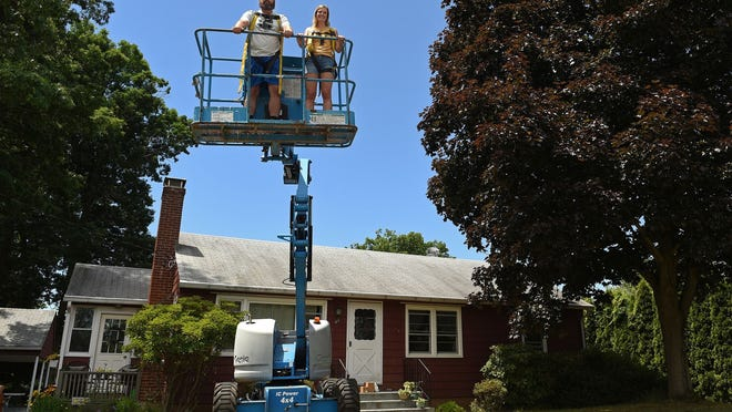 Jon Esmail, left, and Kate Baumann demonstrate how they will use a scissor lift to watch the Travelers Championship from Baumann's Field Road home.
