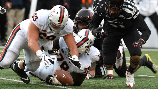 Virginia offensive lineman Chris Glaser (69) dives on a loose ball ahead of Louisville linebacker Trevon Young (91) during the first half of an NCAA college football game, Saturday, Nov. 11, 2017, in Louisville, Ky.
