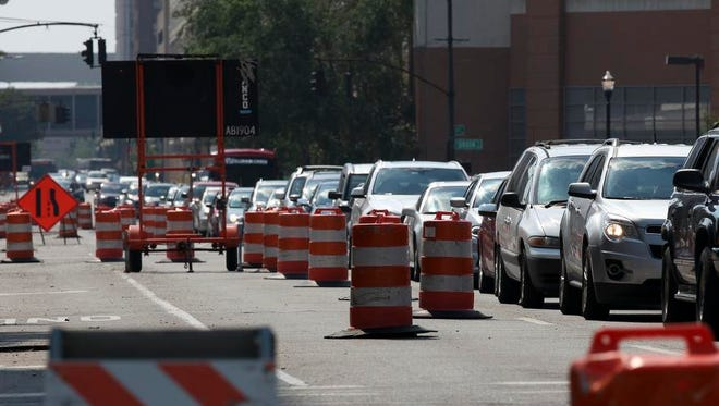 Backed-up traffic and construction barrels are a common sight in downtown Louisville, at sites such as this spot on Liberty Street.
