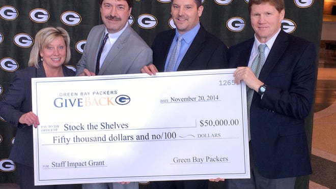 Gannett Wisconsin Newspapers' Stock the Shelves campaign received one of five $50,000 Staff Impact Grants from the Green Bay Packers at a ceremony in the Lambeau Field Atrium November 20, 2014. From left are Cathy Dworak, Packers director of community outreach and player/alumni relations, Mike Knuth, executive editor of Press-Gazette Media, Scott Johnson, publisher of Press-Gazette Media and Mark Murphy, Packers president.