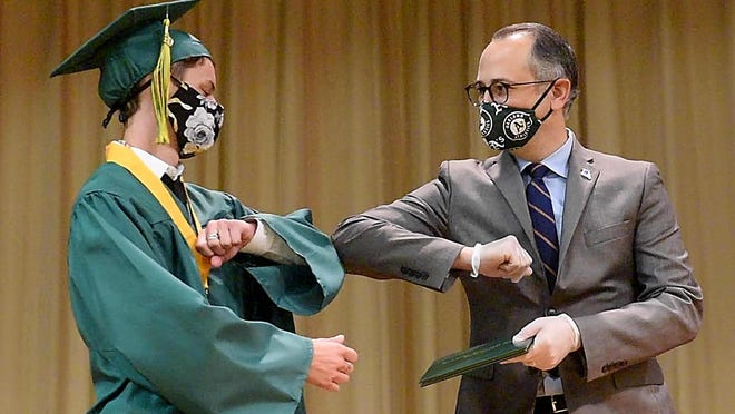 Rock Bridge High School senior Hunter Acton bumps elbows with Columbia Public Schools Superintendent Peter Stiepleman Thursday during the first of five Rock Bridge graduation ceremonies at Rock Bridge High School.