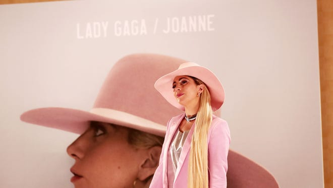 "US singer Lady Gaga poses for photographers in front of her new album cover during a photo call to promote the album ""Joanne"" in Tokyo."