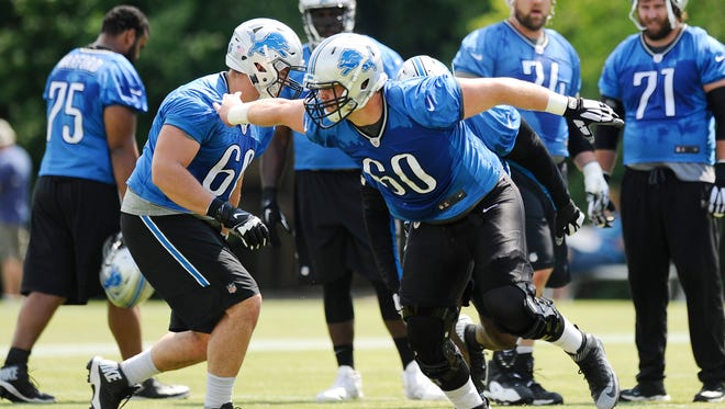 Lions' Graham Glasgow drives off the line during drills.