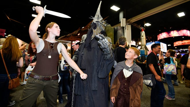 """Fans play around an actor posing in the role of the Witch King of Angmar from the """"Hobbit"""" on day 1 of the 2014 Comic-Con International Convention held Thursday, July 24, 2014 in San Diego."""