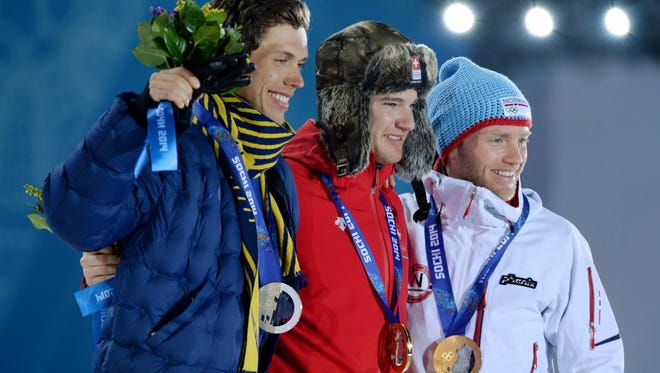 Marcus Hellner, left, Dario Cologna, middle, and Martin Johnsrud Sundby pose in the medal ceremony for the men's 15km skiathlon.