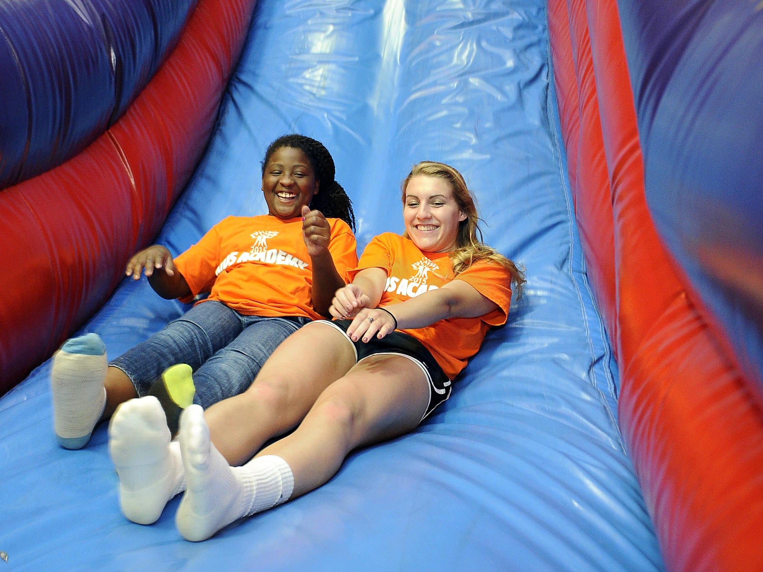 Kandayce Allen, 10, and Miller Fahey slide together at Pump It Up in Franklin. Fahey leads a summer camp for kids at Battle Ground Academy during the summer.