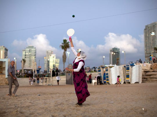 Palestinians play paddleball on the beach during the Muslim Eid al Adha festival, in Tel Aviv, Israel, Tuesday, Sept. 13, 2016. Tens of thousands of Palestinians visited Tel Aviv and other places in Israel after Israel granted travel permits to West Bank Palestinians.