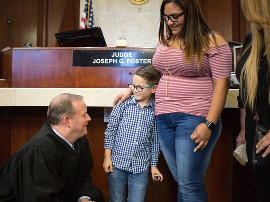 Judge Joseph G. Foster meets personally with 7-year-old Angel, who was officially adopted by Christine Rodriguez, right, at the Collier County Courthouse on Friday, Nov. 17, 2017.