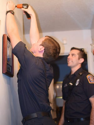 Escambia County Fire Rescue workers install a smoke alarm.
