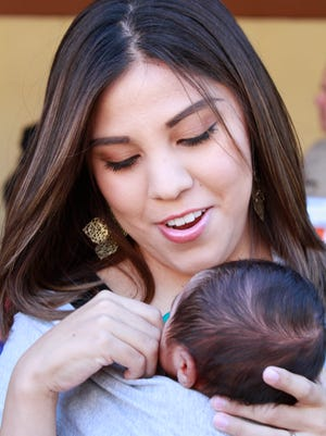 Gabi Aguirre Miramontes, daughter of slain Deputy Peter J. Aguirre Jr., holds her 1-month-old son, Samuel Peter Miramontes, at Friday's ceremony.