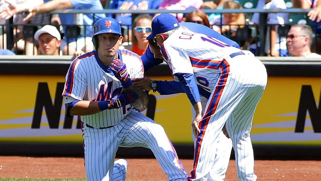 New York Mets shortstop Asdrubal Cabrera (13) is tended to after being injured against the Philadelphia Phillies during the first inning at Citi Field on Sunday, Aug. 28, 2016. The Phillies won 5-1.