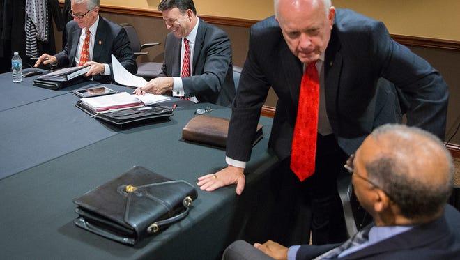 Frank Hancock (red tie) speaks to fellow Ball State University trustee Hollis Hughes during a meeting last week.