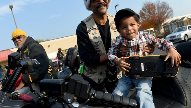 Quentin Jacobs, 3, holds on to his toy car as he sits on the motorcycle of Darryl Maxfield, rear, of the Buffalo Soldiers Cavalry Scouts Motorcycle Club of Pa. The club, along with three other motorcycle clubs, rode into the parking lot of the York Day Nursery and delivered toys to the children from ages ranging from newborn to 10-years-old on Saturday.