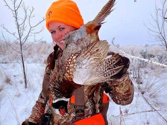 Michelle Bodenheimer holds a ring necked pheasant harvested