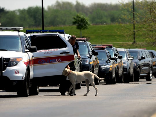 A Columbus firefighter puts his K-9 partner into their vehicle Monday morning, May 7, 2018, at Amanda-Clearcreek High School in Amanda. The school was evacuated while law enforcement officers searched the building after a bomb threat was found in a boys bathroom.