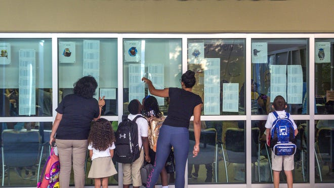 Parents and children look for their class assignments at Pine Jog Elementary in West Palm Beach on the first day of school in August 2018.