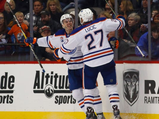 Edmonton Oilers center Connor McDavid, back celebrates his goal with left wing Milan Lucic during the third period of an NHL hockey game against the Colorado Avalanche on Wednesday, Nov. 23, 2016, in Denver. (AP Photo/David Zalubowski)