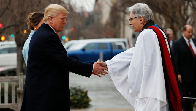Rev Luis Leon greets President-elect Donald Trump and his wife, Melania, as they arrive for a church service at St. John's Episcopal Church across from the White House in Washington, Friday, Jan. 20, 2017, on Donald Trump's inauguration day.