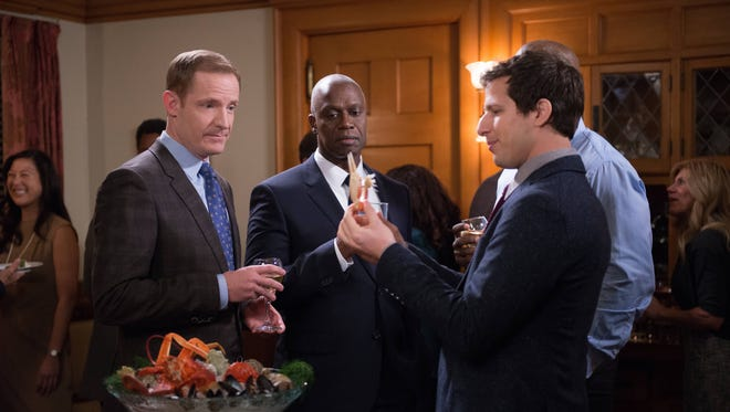 Capt. Holt (Andre Braugher, center) invites Peralta (Andy Samberg, right) and the rest of his detectives home to meet his husband (Marc Evan Jackson) on 'Brooklyn Nine-Nine.'