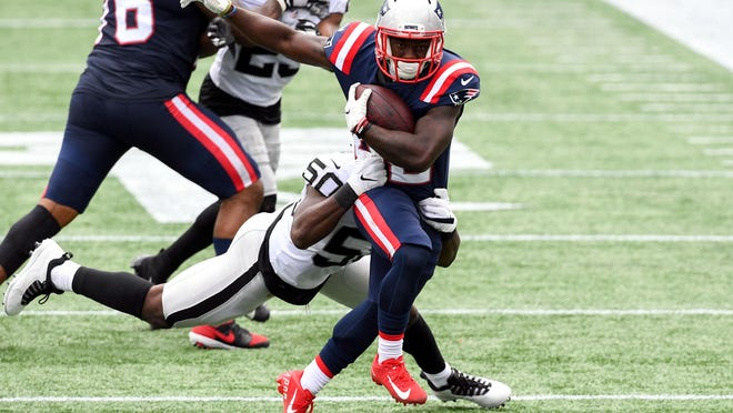 Patriots running back J.J. Taylor (42) is tackled by Raiders linebacker Nicholas Morrow during the second quarter of the Sept. 27 game at Gillette Stadium. Taylor wears the name of his friend, Tank Goodman, on his helmet to honor his former teammate.