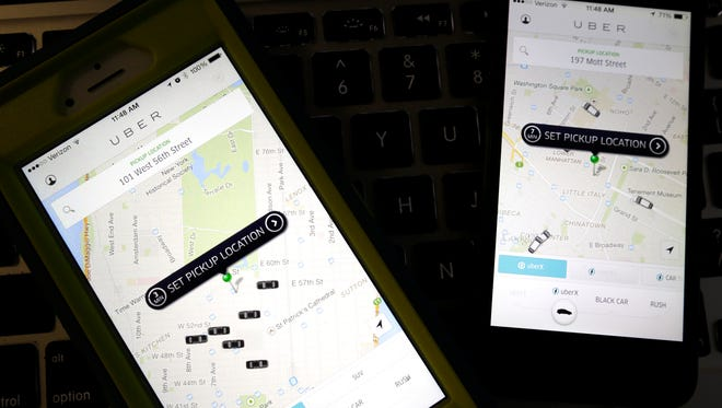 Smart phones displaying Uber car availability in New York.